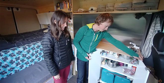 Couple opening kitchen cabinet in van conversion