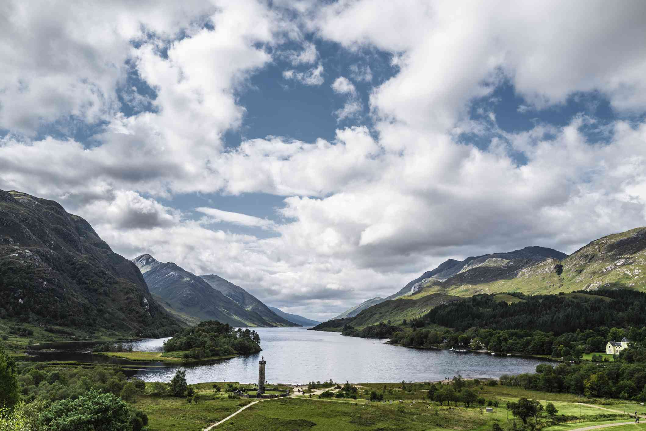 View from above Loch Sheil, surrounded by mountains with green lawn in the foreground under a blue sky with white clouds