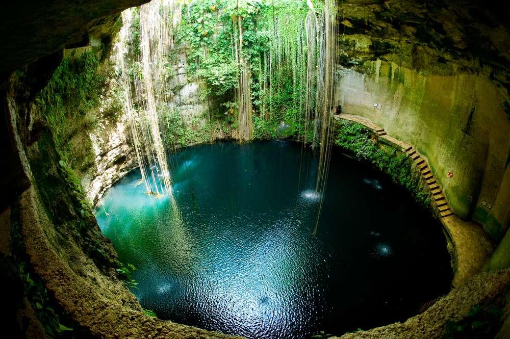 The circular Cenote Ik Kil with greenery climbing down its walls