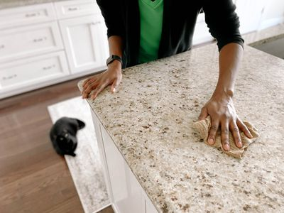A woman wiping down a granite kitchen counter.