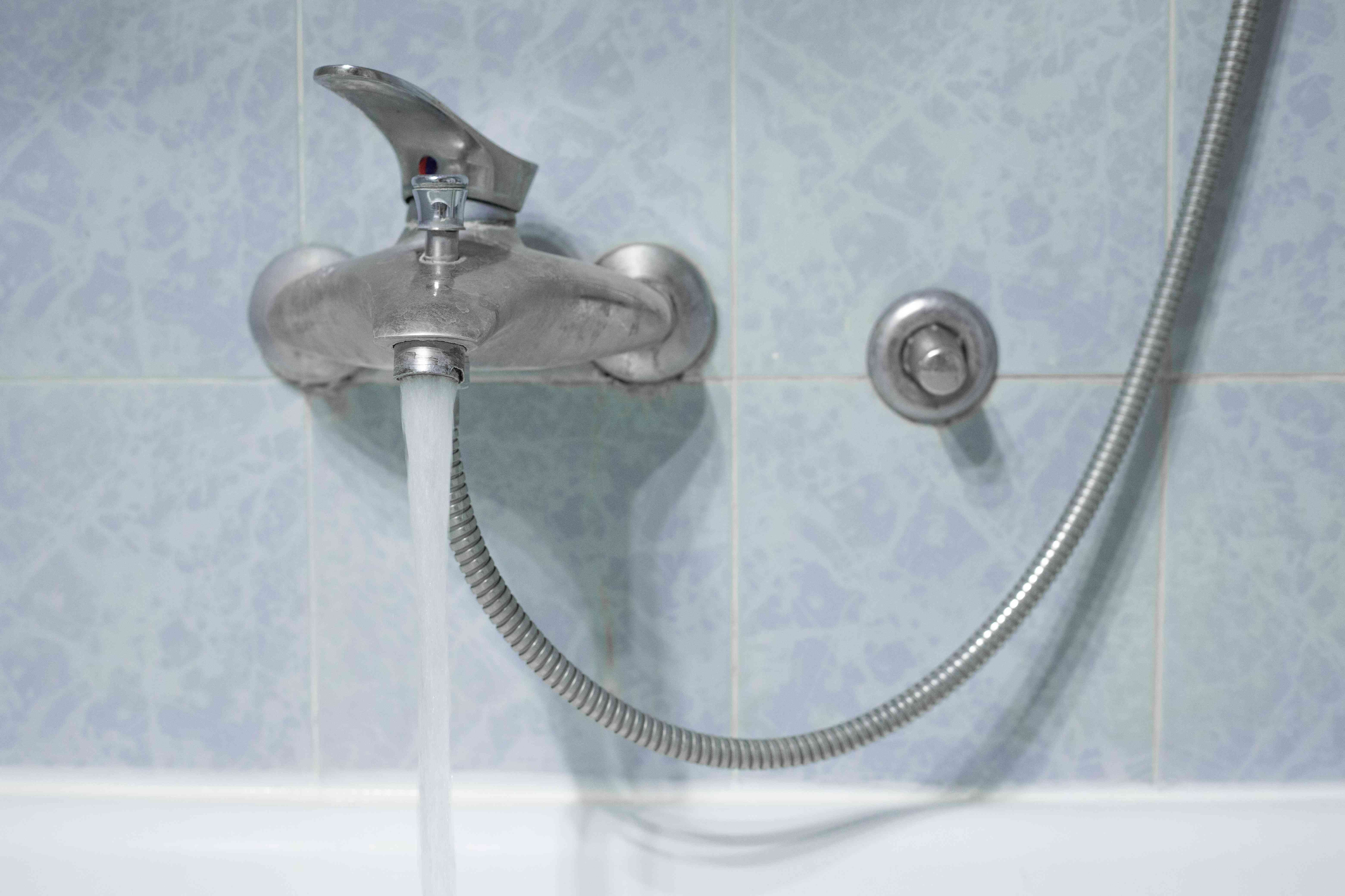 water faucet in bathtub turned on full stream with shower attachment