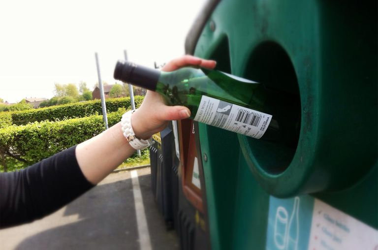 Recycling glass bottle in public bottle bank