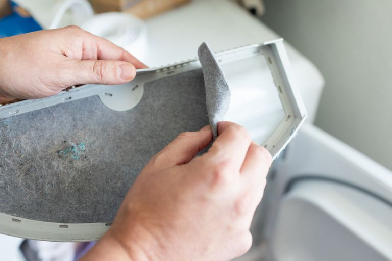 hand peels away layer of gray dryer lint from dryer filter