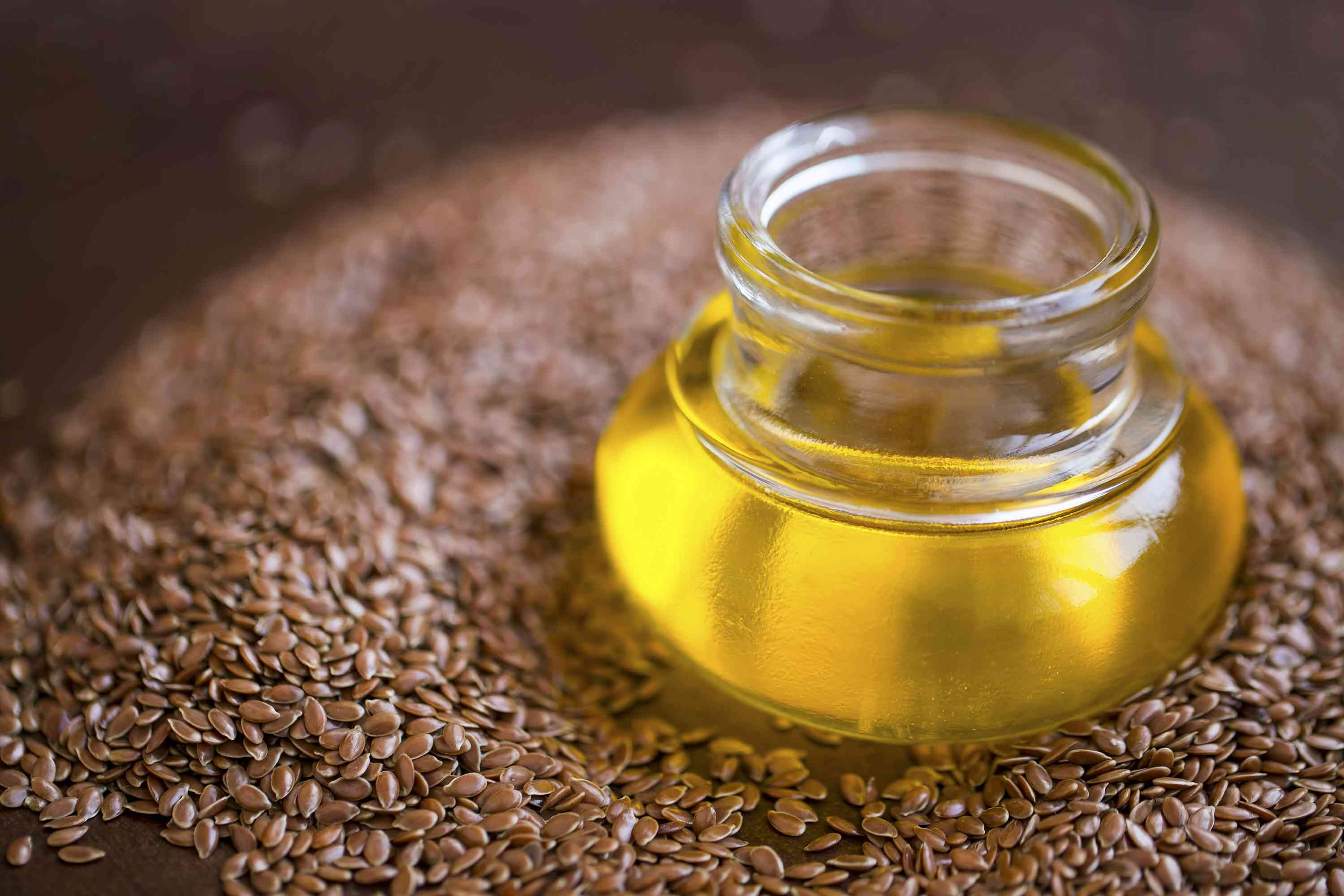 Flax seed oil with flax seeds closeup, selective focus, raw flaxseed oil medicinal oil alternative medicine, omega 3 rich oil