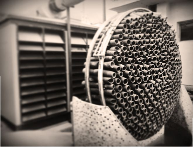 Black and white photo of circular installation of terracotta tubes