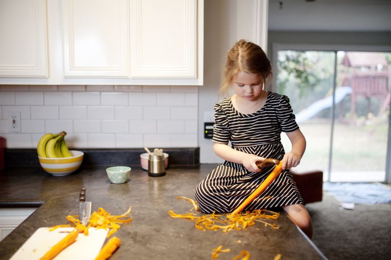 child peels carrots on countertop