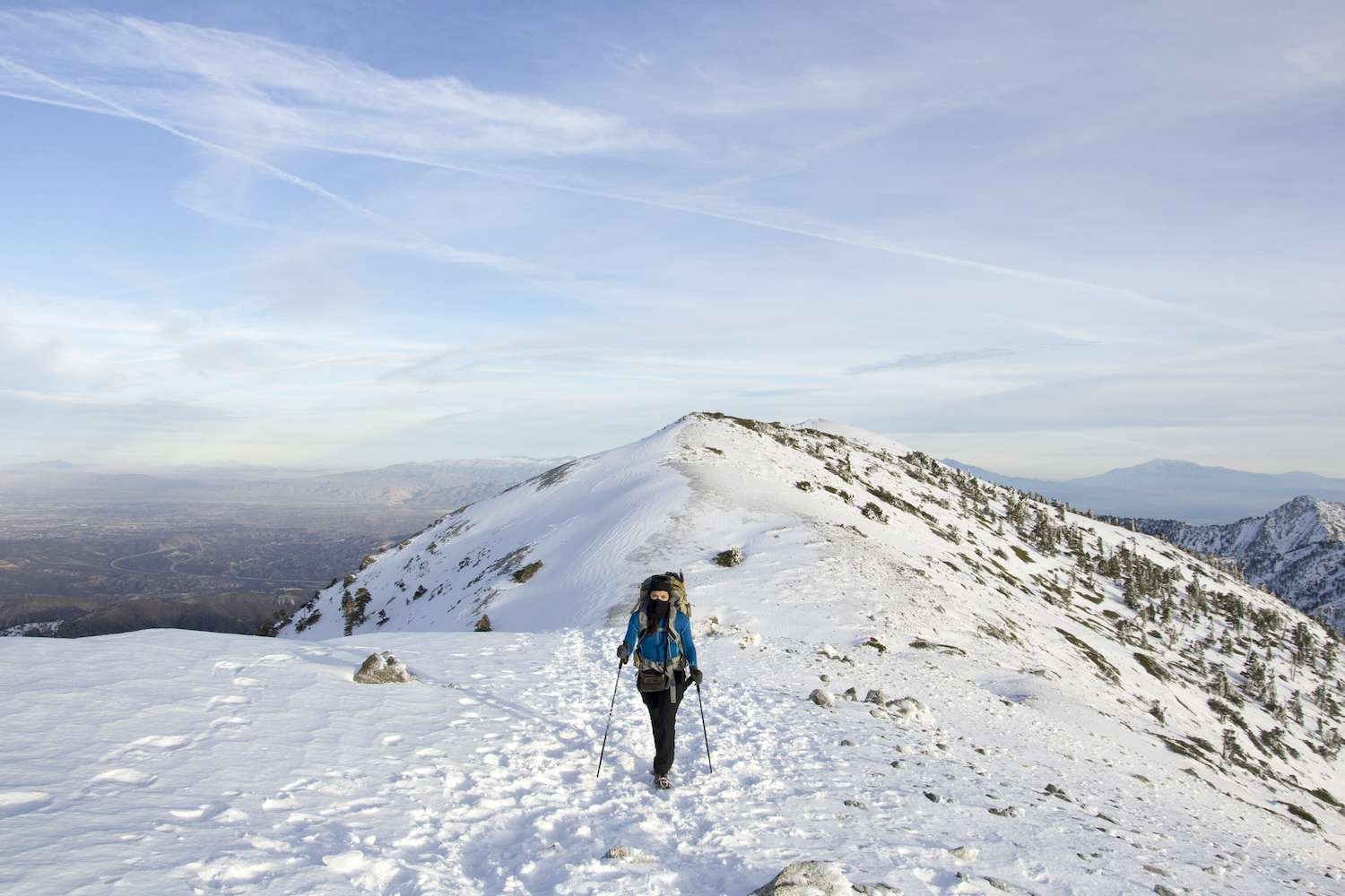 A hiker poses in front of the snow-capped summit of Mount San Antonio.