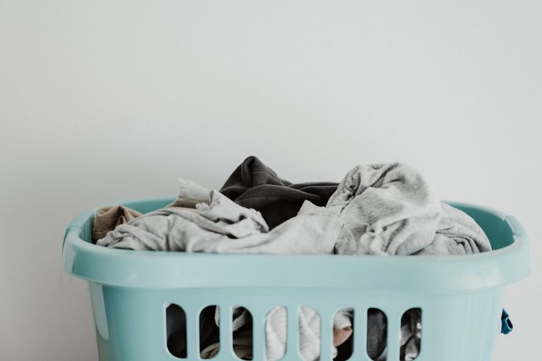 Baby blue plastic laundry basket filled with dirty clothes