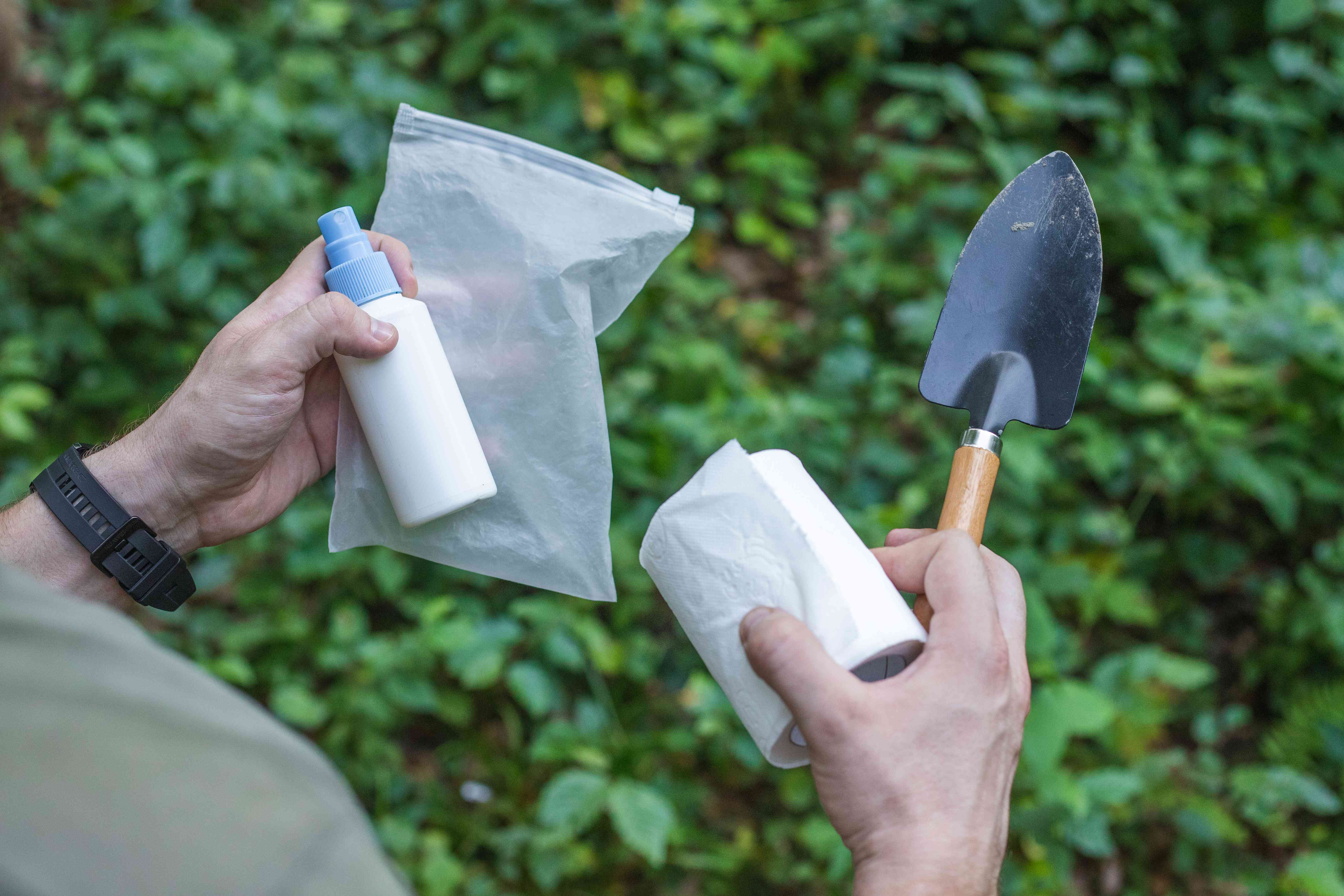 guy holds tools for going to the bathroom outside, including toilet paper and small garden spade