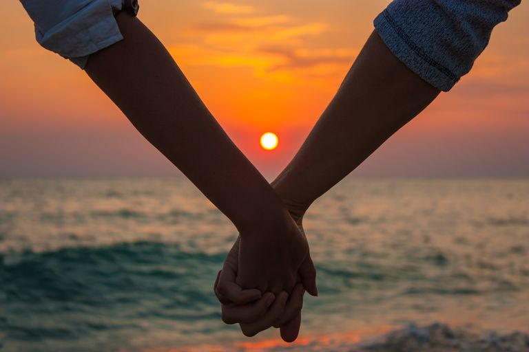 A couple holding hands at sunset
