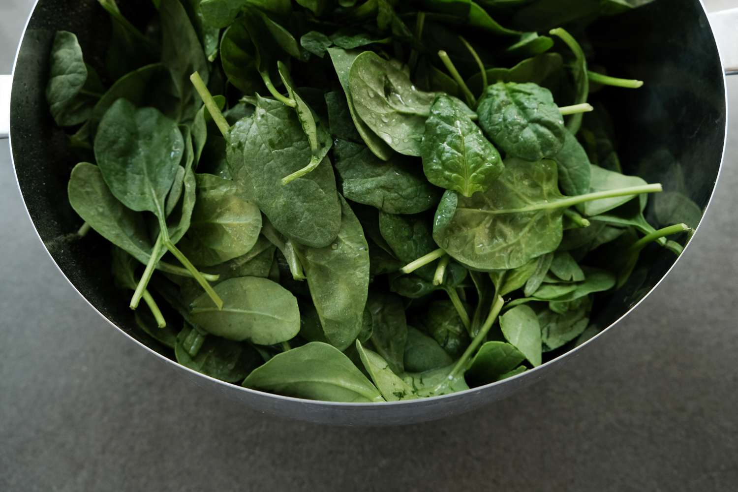 fresh spinach in metal bowl`