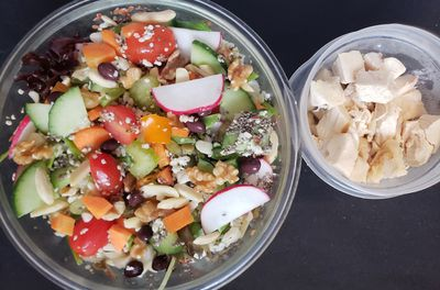 large bowl of salad and a small container of fresh mozzarella cheese