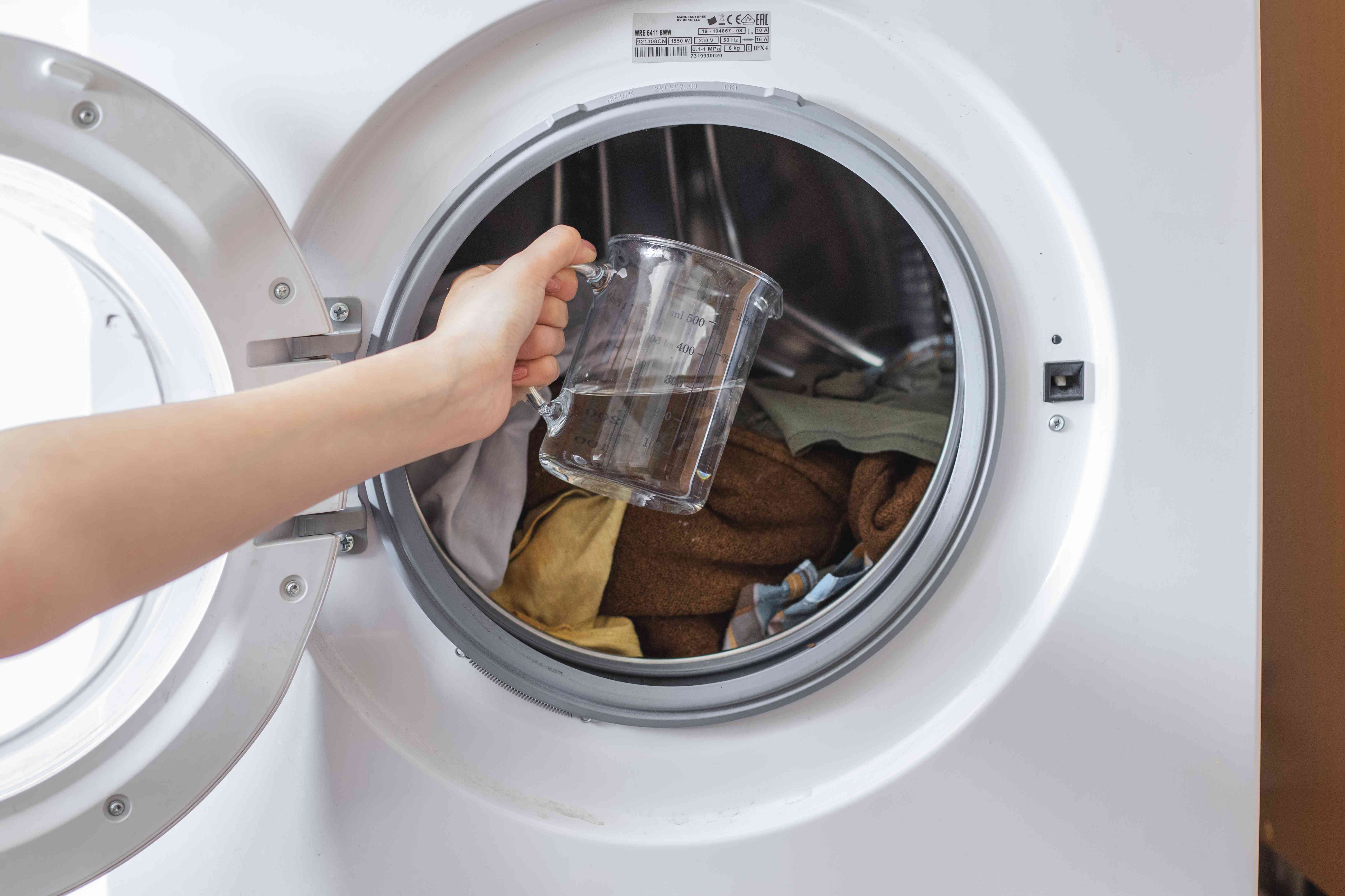 open washing machine door with hand holding pitcher of vinegar to pour on dirty clothes