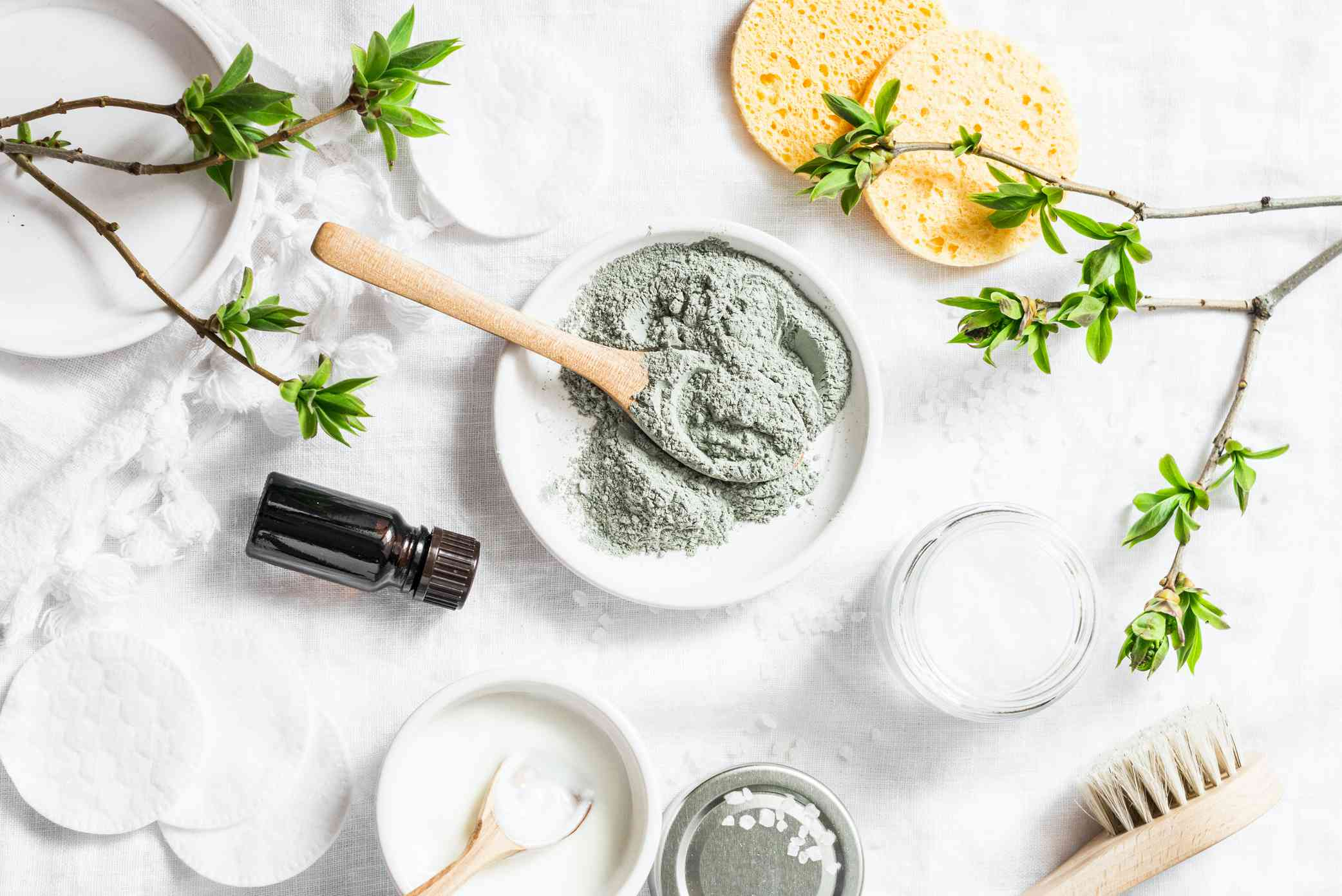 Bowl of bentonite clay surrounded by beauty ingredients and tools