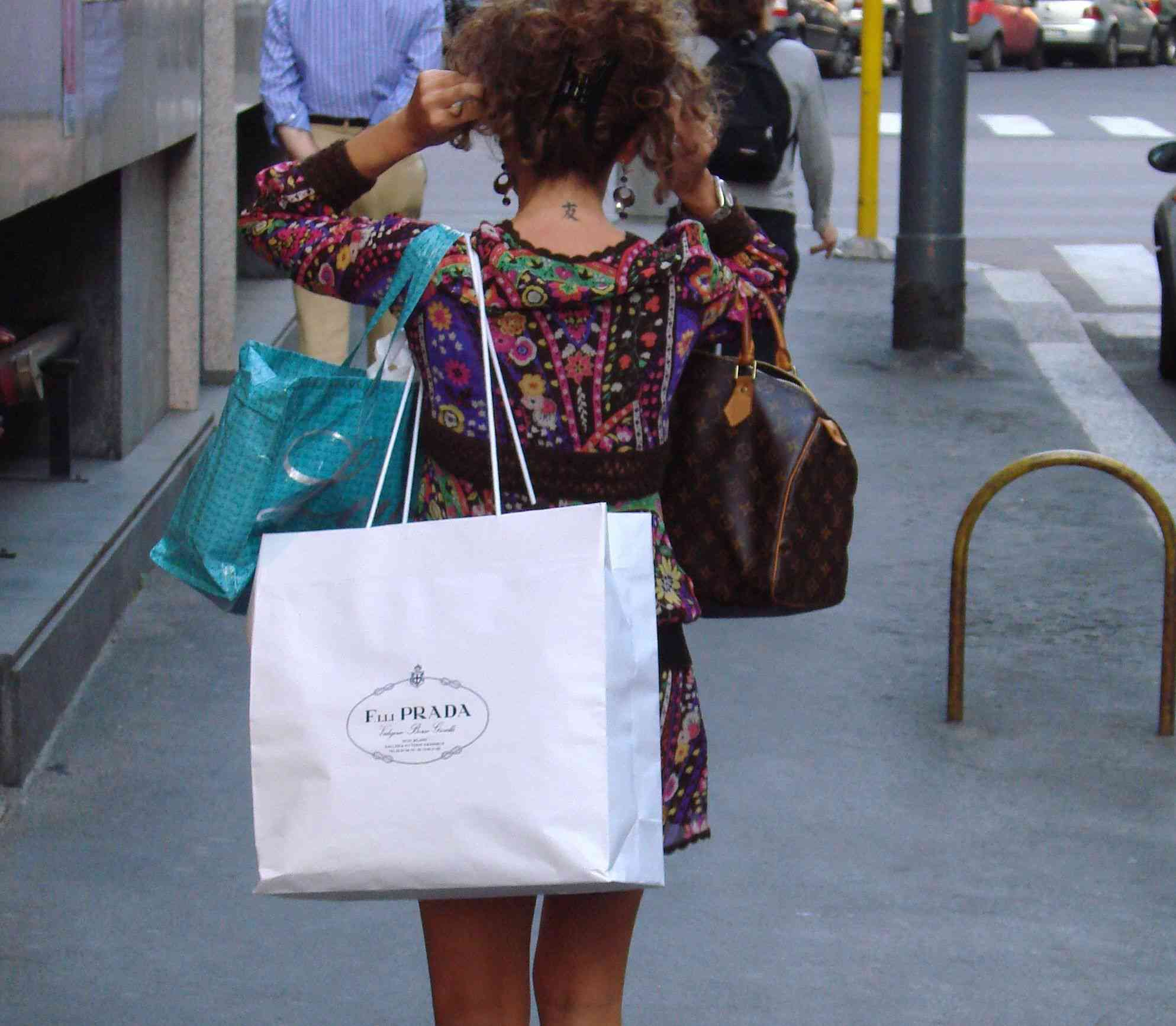Woman walking down the sidewalk with shopping bags and a designer purse