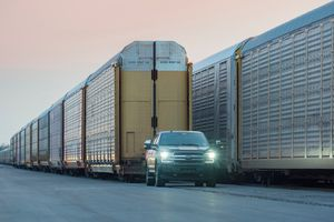 Ford truck driving in front of a train