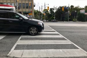 Car at stop light sitting on top of pedestrian crosswalk