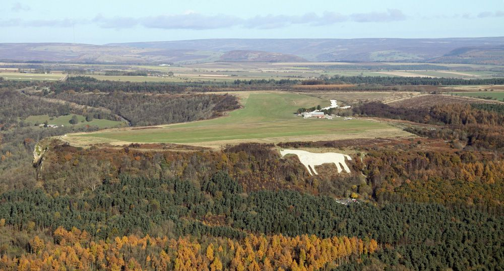 Aerial view of Kilburn White Horse limestone carving on a green hill surrounded by gold and green trees on the surrounding hills beneath a bright blue sky