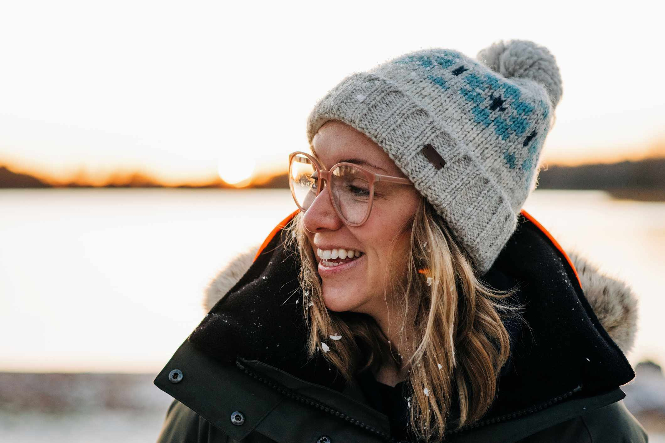 A white woman wears a hat with pom pom outside in the winter.