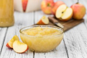 small glass bowl of applesauce, apples in background
