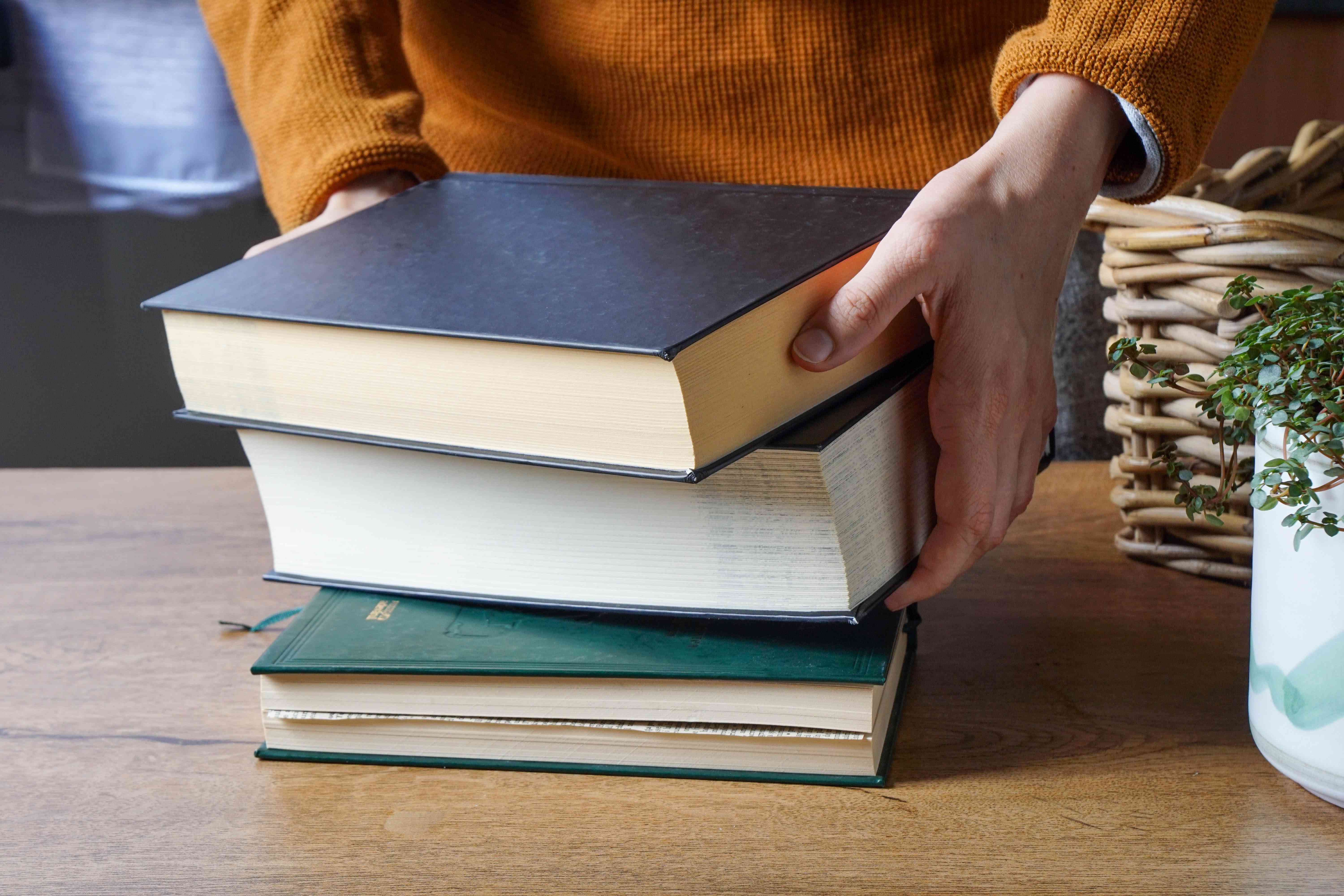 person in orange sweater places heavy books to press flowers in book on bottom
