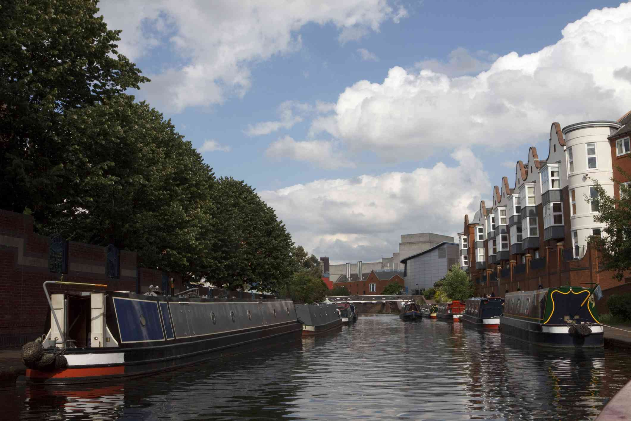 canal in Birmingham,England with buildings on one side and trees on the other