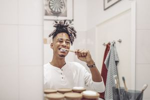 Man brushing his teeth with a natural toothbrush and toothpaste