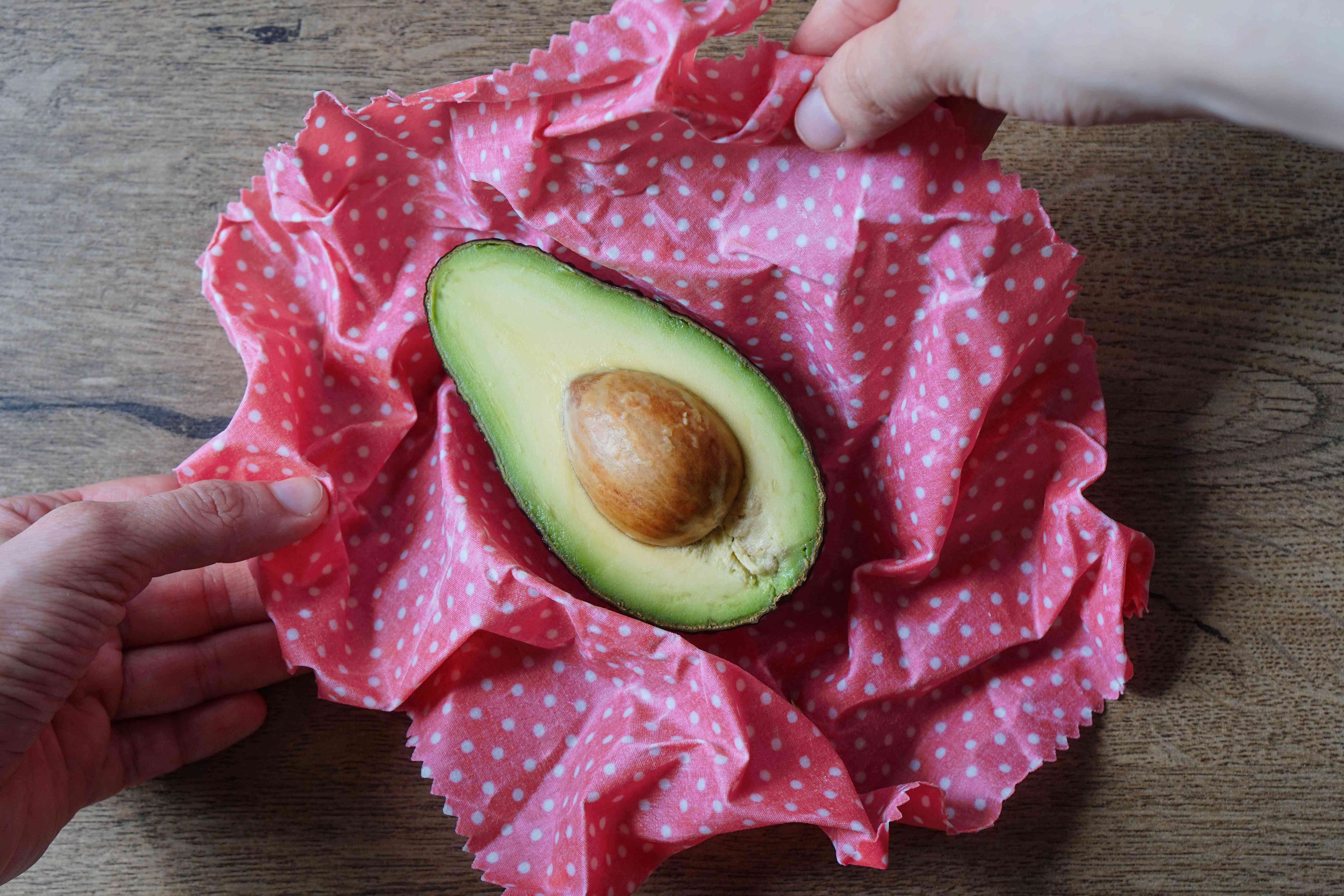 cut avocado with seed about to be stored with polka dot beeswax wrap