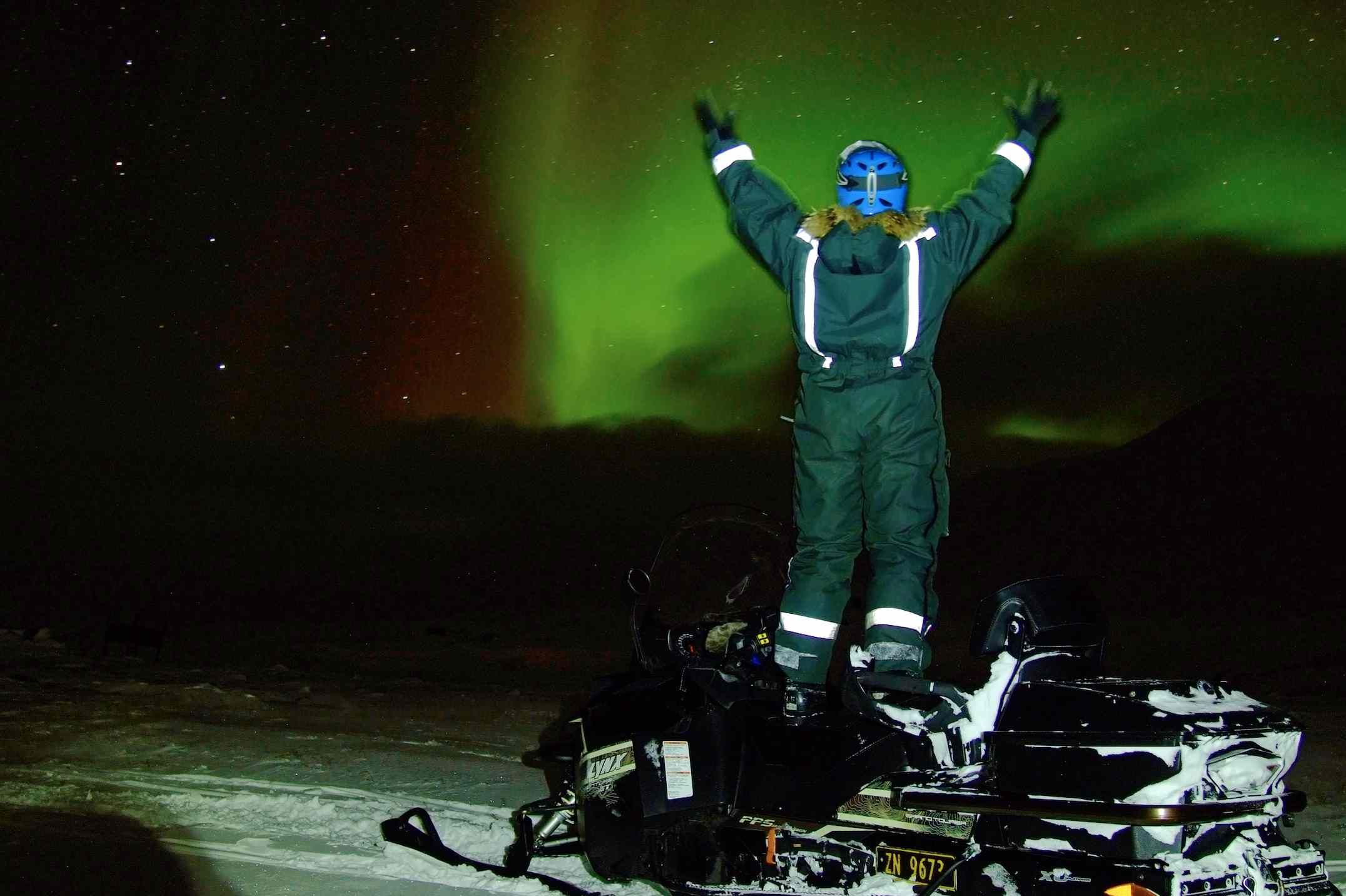 Watching the Northern Lights from atop a snowmobile.