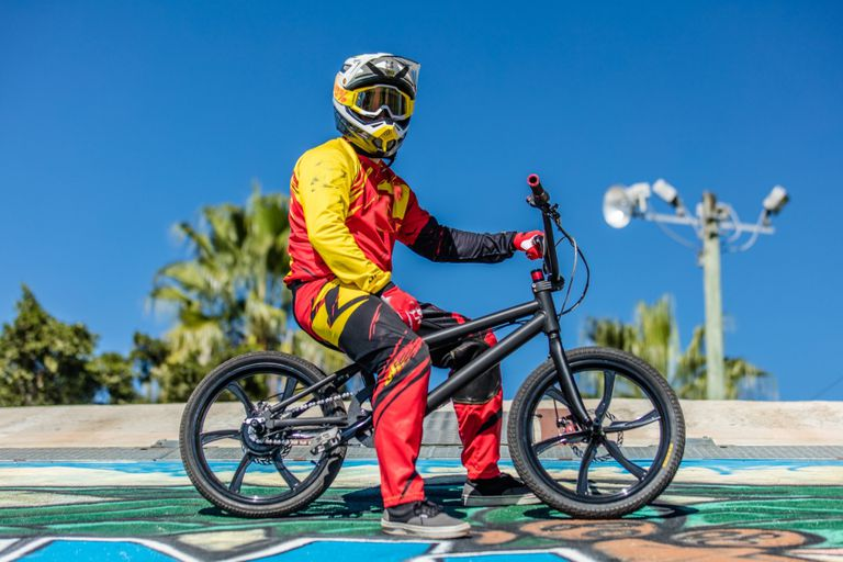 Person wearing colorful suit, goggles and helmet, sitting on an electric BMX bike made by Life Electric Vehicles