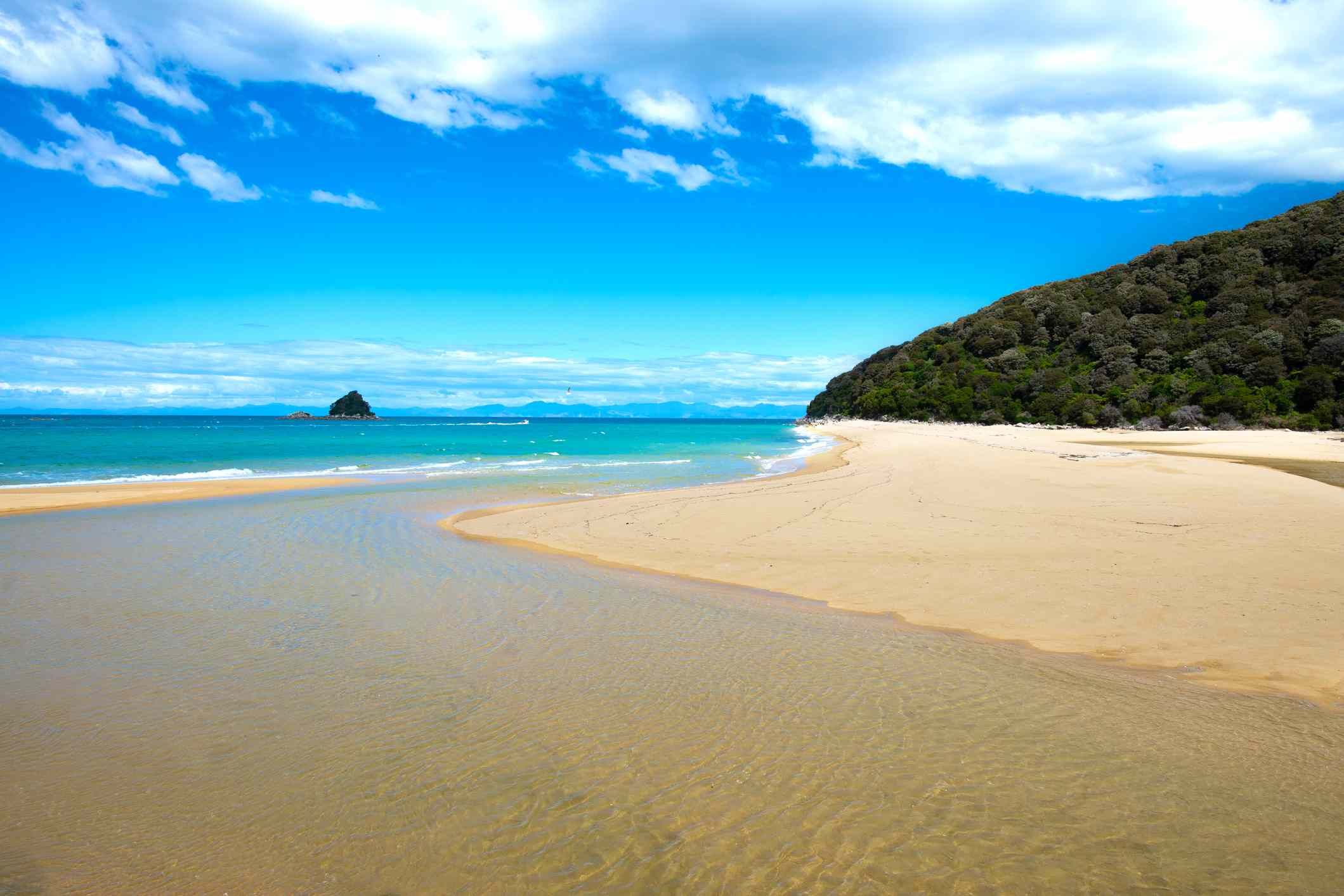 a wide, cream-colored stretch of beach along a blue/green sea with a lush, green mountain in the distance and a bright blue sky with high clouds at Abel Tasman National Park