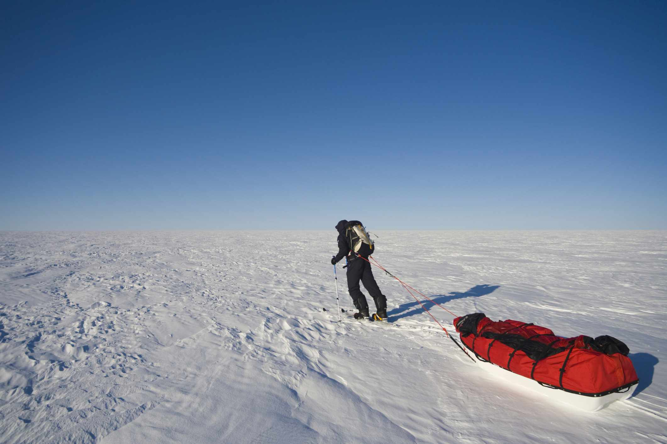 A researcher pulls his gear across a vast snow-covered ice sheet.