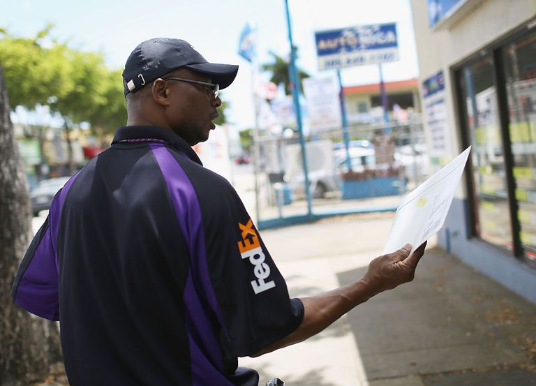 A FedEx worker looks at an envelop that needs to be delivered.