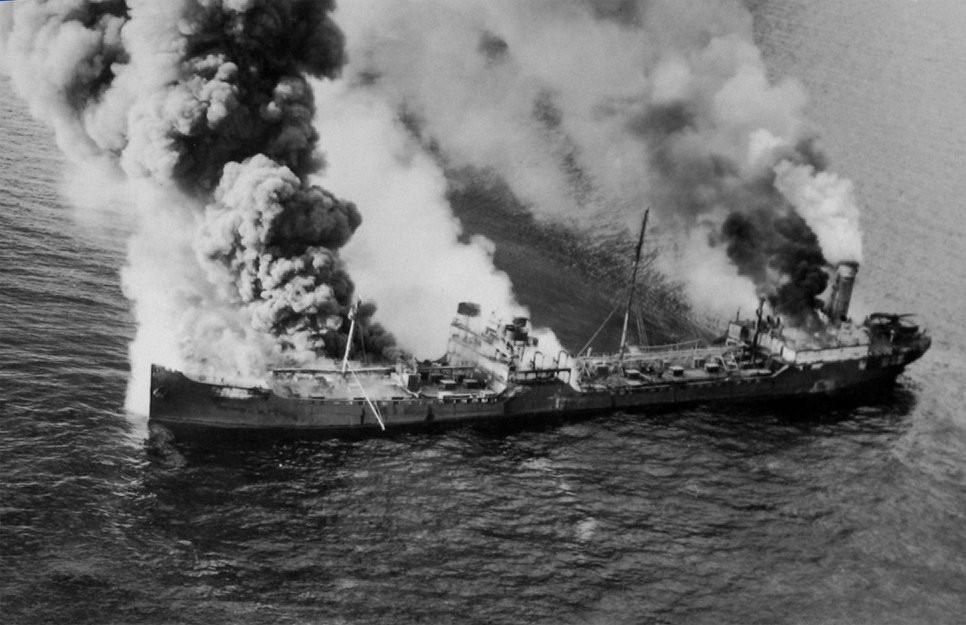 A black-and-white photo of a burning tanker ship that is beginning to sink
