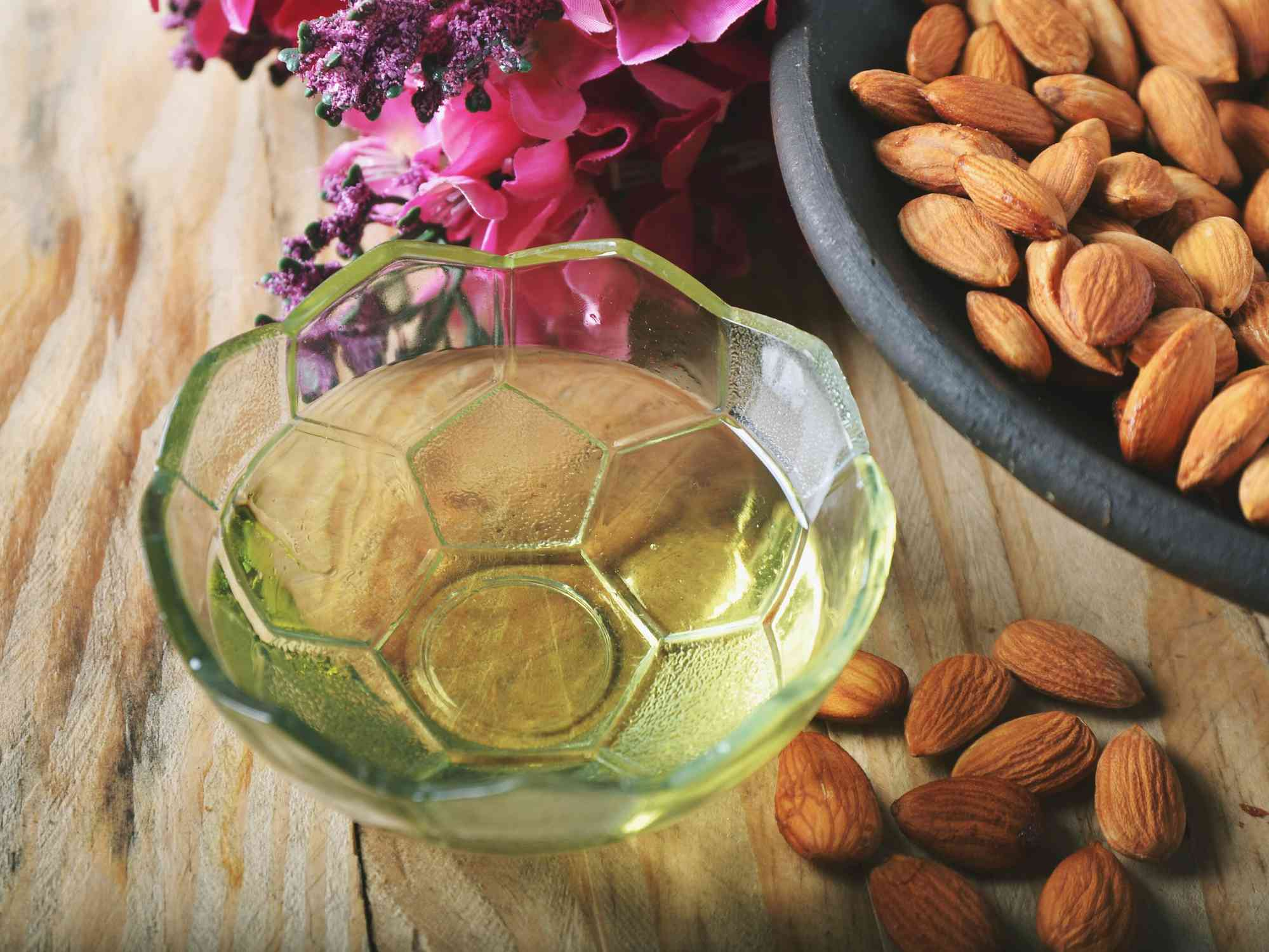 High Angle View Of Almonds And Oil In Bowl Over Table