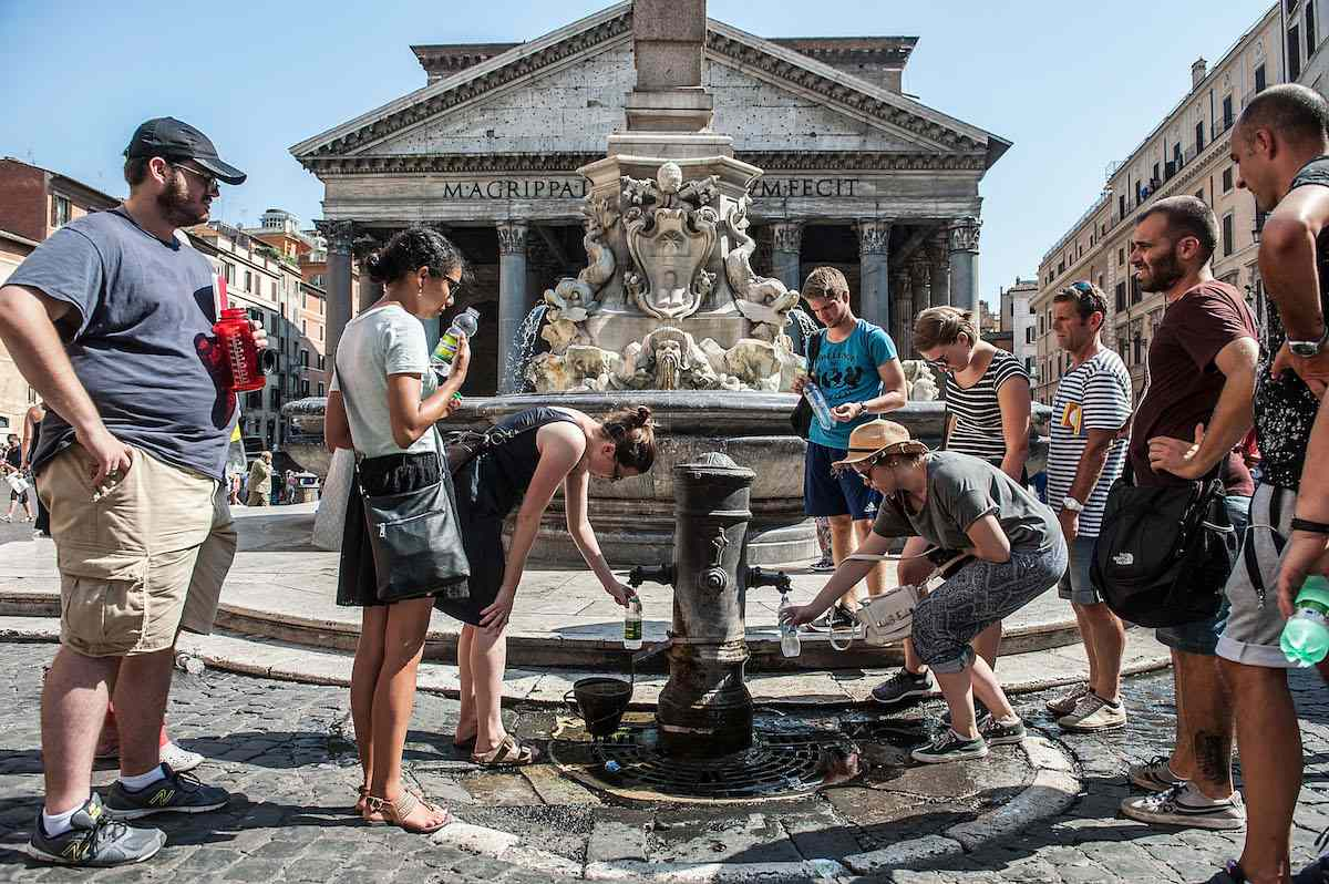 Tourists fill bottles of water in a fountain at Piazza del Pantheon as temperatures rise in 2015 in Rome, Italy.