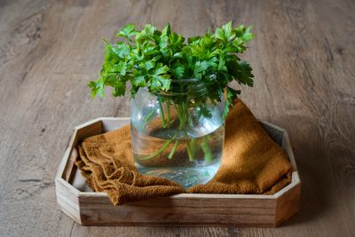 glass jar filled with water holds fresh parsley, sits on brown cloth and tray