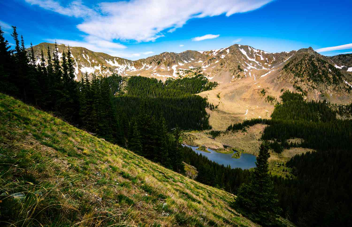 The view of snow-covered mountains and the reflective waters of a lake from Wheeler Peak near Taos, New Mexico