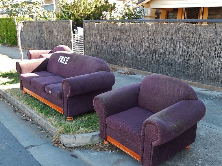 """Purple couch with """"free"""" written on it in tape and a chair on a curb"""
