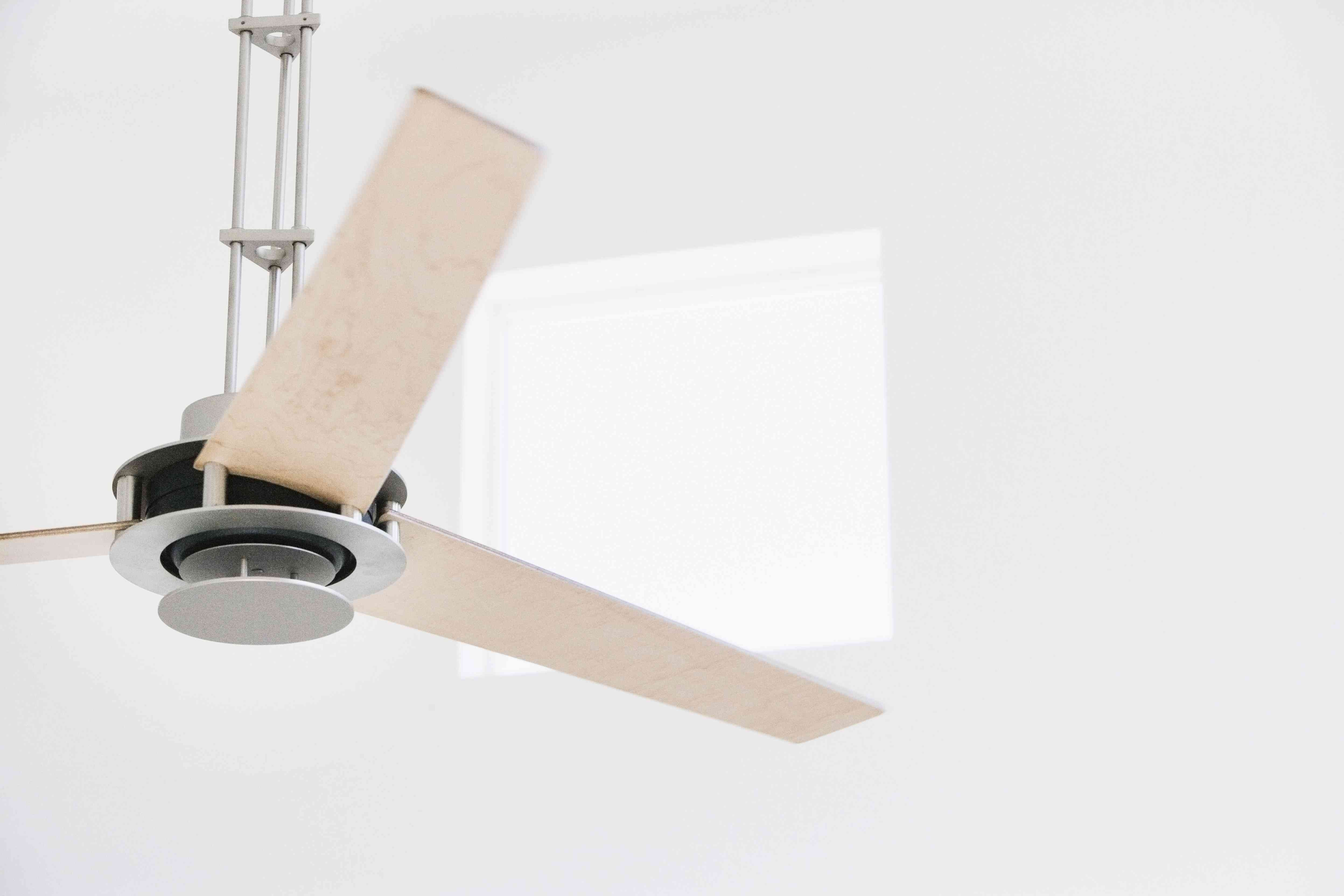 A metal and wood ceiling fan in a white room
