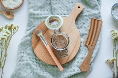diy homemade dry shampoo in glass jar with makeup brush, comb, and towel