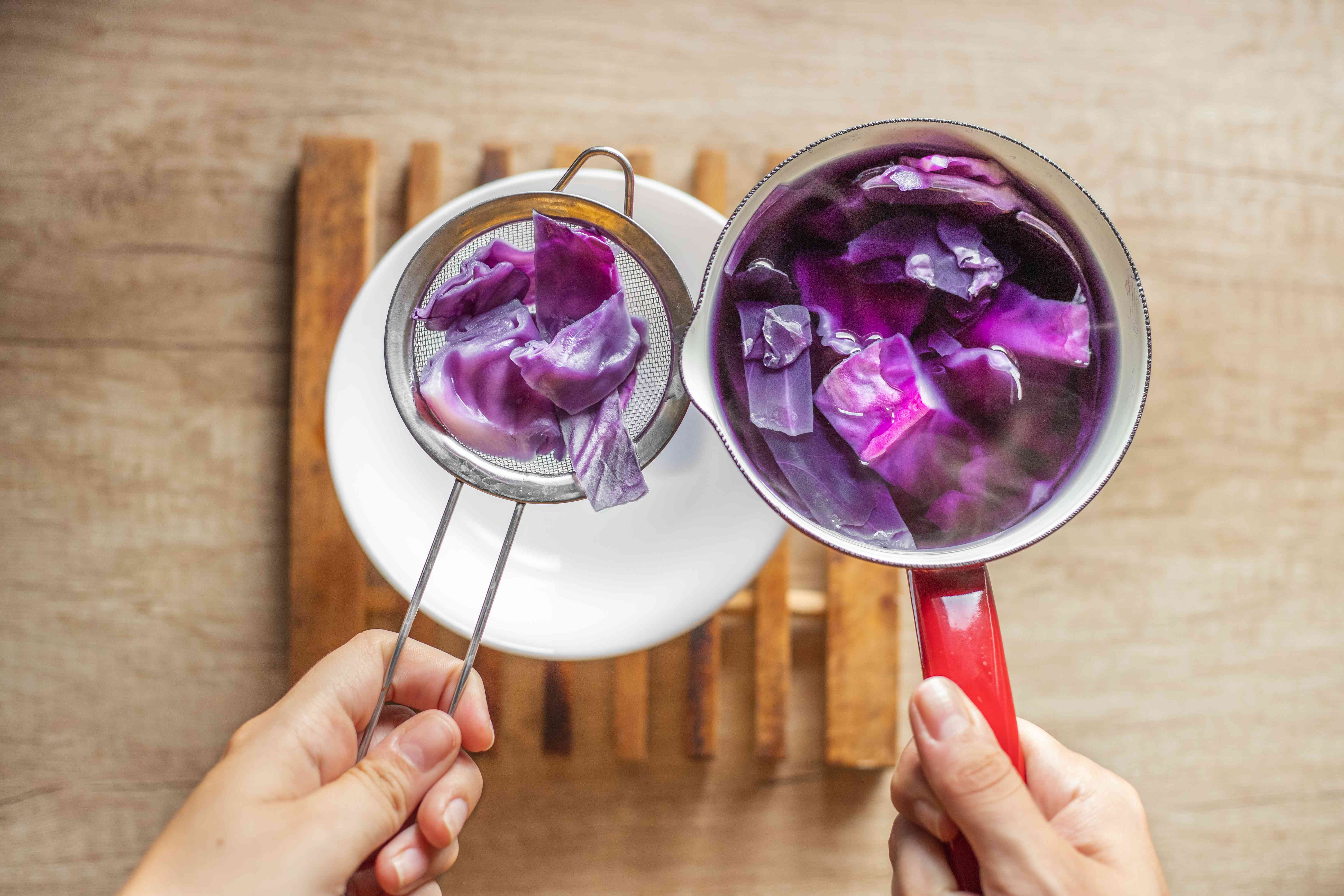 a sieve is used to strain red cabbage out of boiled purple water into bowl