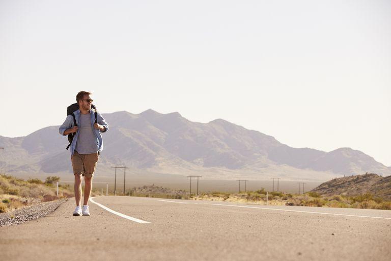 A man with a backpack walks along a desert highway.