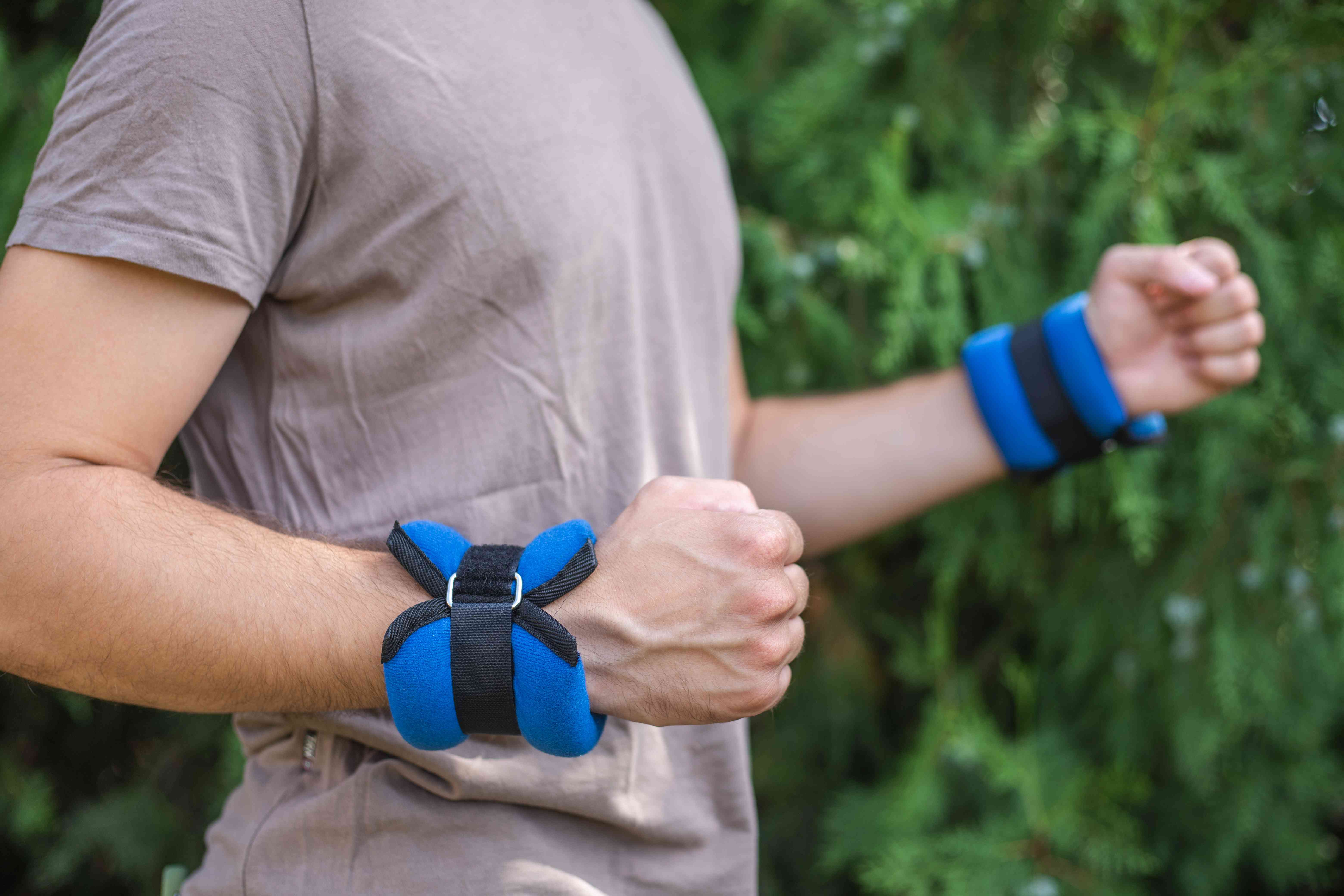 man in t-shirt wears blue velcro-strapped arm weights while walking outside