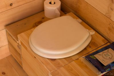 A compostable toilet in a wood cottage washroom.