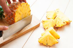 Pineapple being chopped by a knife on a wood cutting board.