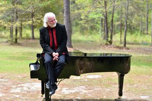 Chuck Leavell sitting on a piano in the woods.