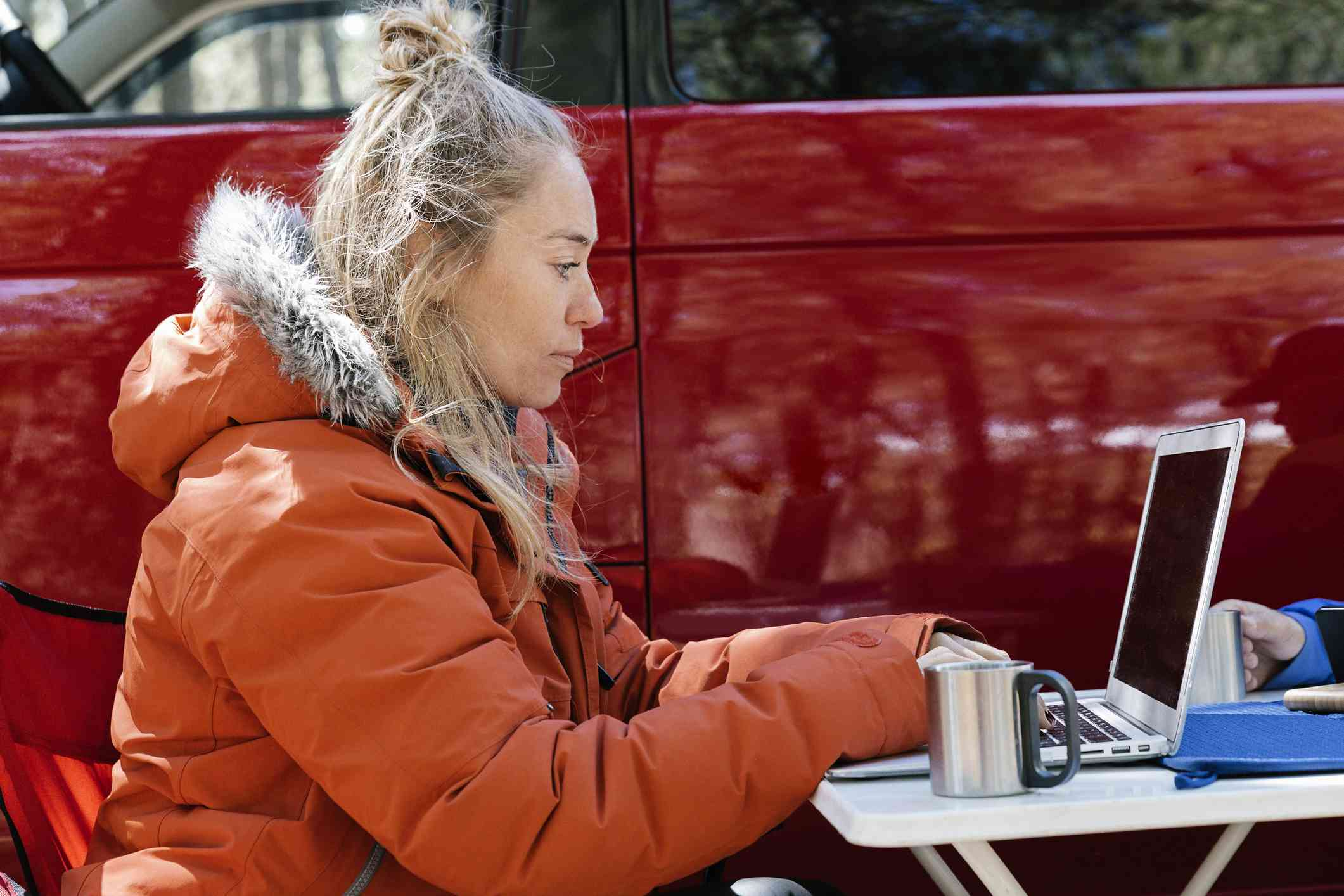 Person working on laptop outside of van