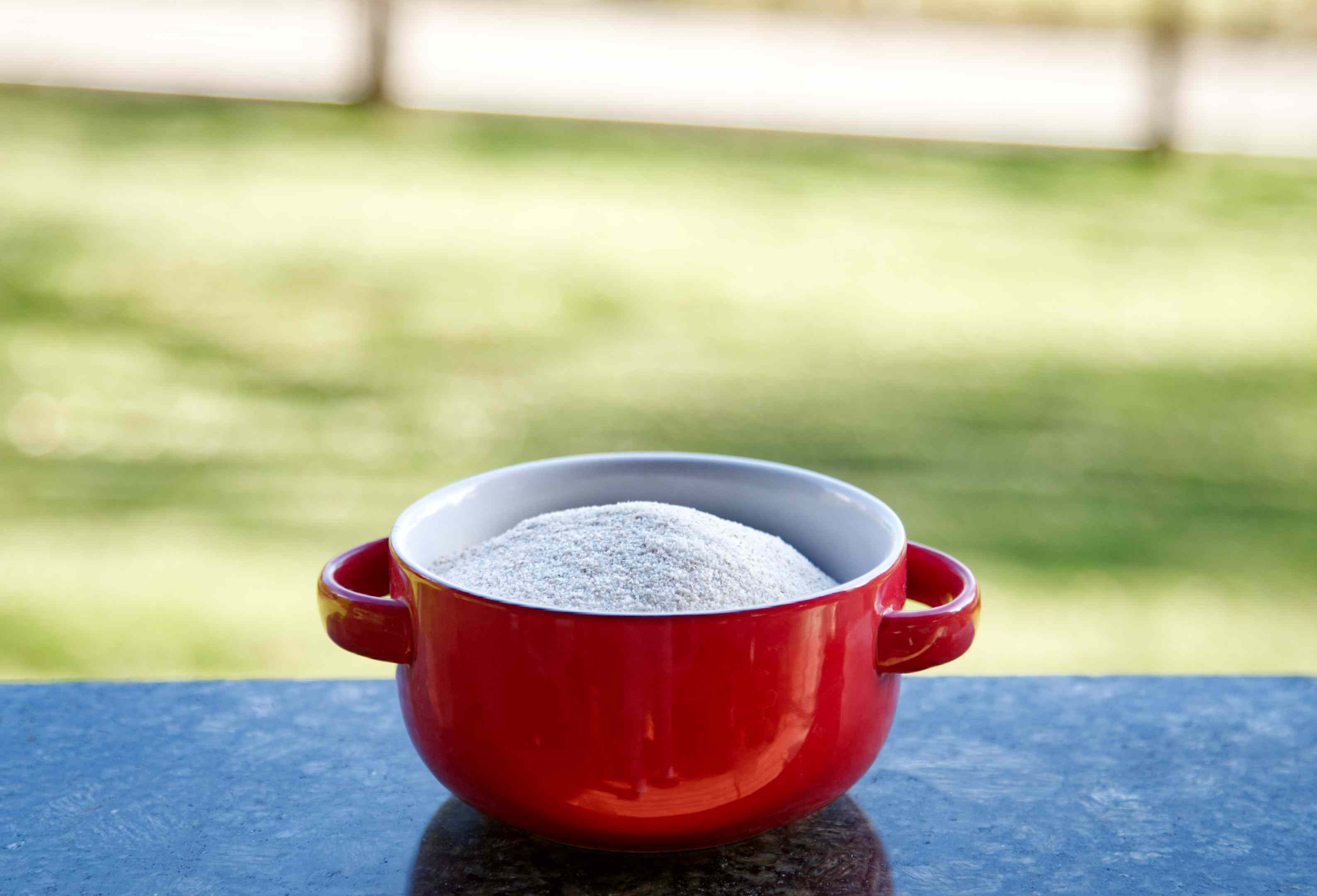 uncooked cream of wheat in red ceramic bowl with handles outside on granite table