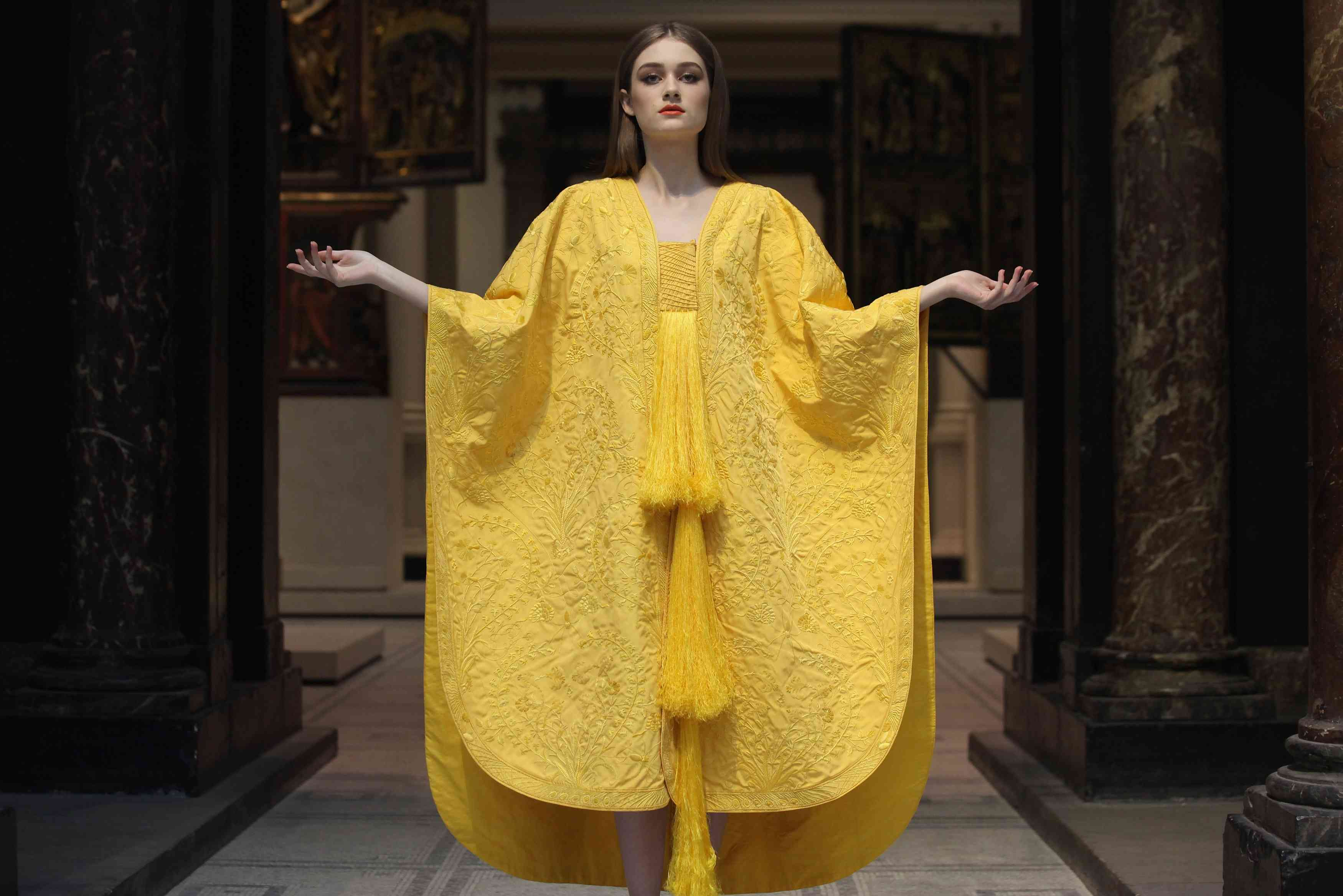 A model wearing a yellow cape made from spider silk
